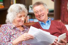 Senior Couple Looking At Domestic Finances Together - stock photo