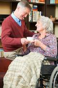 Senior Man Giving Wife In Wheelchair Cup Of Tea Stock Photos