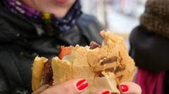 Woman eating big fresh juicy burger in a street fast food closeup Stock Footage