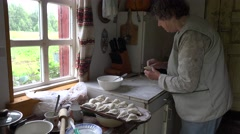 Senior grandma woman prepare dumplings with curd in rural kitchen room. 4K Stock Footage