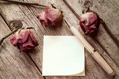 Old roses and blank sticky note - stock photo