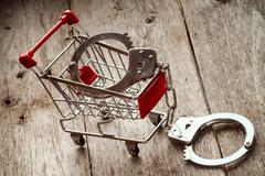 Shopping cart and handcuffs Stock Photos
