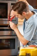Man Repairing Domestic Oven In Kitchen - stock photo