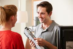Engineer Giving Advice On Installing Digital TV Equipment - stock photo