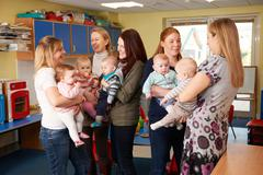 Group Of Mothers With Babies Meeting At Playgroup - stock photo