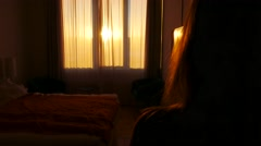 Steadicam shot of woman opening windows curtains meeting sunrise, hotel Stock Footage