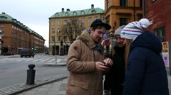 Three young friends looking at city map in smartphone, planning where to go in Stock Footage
