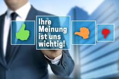 Your opinion (in german language) touchscreen is operated by businessman Stock Photos
