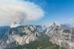 View from Glacier Point to the Yosemite Valley forest fire with smoke left Half - stock photo