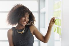 Portrait of a smiling business woman with an afro in bright glass office - stock photo