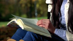 Slowmotion detail of young beautiful happy woman sits in park and reads a book Stock Footage