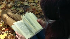 Slowmotion woman holds and browses through the book in the park Stock Footage