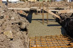 Concrete is spreading in foundation over reinforcing steel bars. Stock Photos