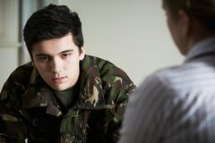 Soldier Suffering With Stress Talking To Counselor - stock photo