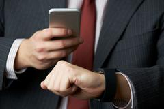 Businessman Synchronizing Smart Watch With Mobile Phone - stock photo