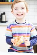 Young Boy Eating Sugary Donut For Snack Stock Photos