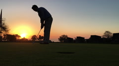 Golfer misses a putt at sunset Stock Footage
