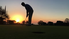 Golfer makes a putt at sunset Stock Footage