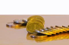 Stack of coins close-up on a gold background - stock photo