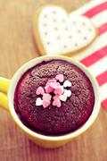 Chocolate mug cake and heart-shaped cookie, filtered Stock Photos