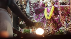 Hare Krishna statues with candles at foreground - stock footage