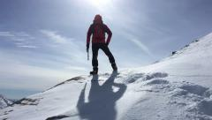 Mountaineer climbing a snowy peak in winter season. Stock Footage