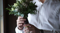 man holding a beautiful bouquet in the hands of; your watch - stock footage