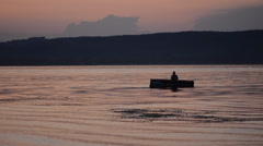 Silhouette of fisherman in a boat Stock Footage