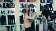 Woman trying on shoes in a shop Stock Footage