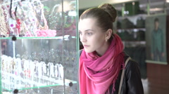 Pretty girl examining showcase of jewels in shopping center. 4K Stock Footage