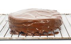Chocolate icing dripping off from cake on grid - stock photo