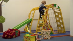 4K toddler playing sports to children's entertainment area with stairs Stock Footage
