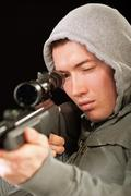 Sniper in hood aims at rifle - stock photo