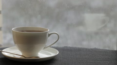 White  cup with steaming tea is in front of the window. Stock Footage