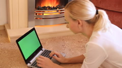 Girl looks in the laptop by the fireplace Stock Footage