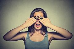 Young woman with eyes painted on her hands isolated on gray wall background Stock Photos