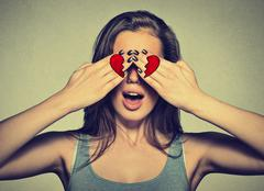 Beautiful young woman eyes covered by hands with broken heart printed on them - stock photo
