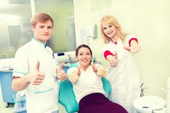 Woman giving thumbs up at dentist office. Stock Photos