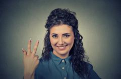 Portrait of young pretty woman giving a three fingers sign gesture Stock Photos