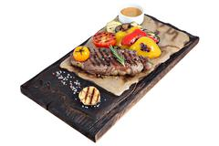 Ribeye steak on parchment paper and board from burnt wood. Stock Photos