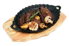 Flank steak baked in an oval cast iron plate - stock photo