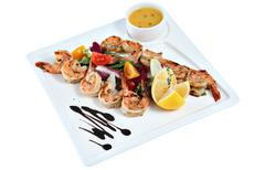 Prawns grilled with vegetable on square ceramic serving dish isolated. - stock photo