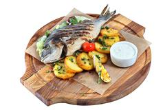 Fried fish dorade on wooden board with parchment and potatoes. - stock photo