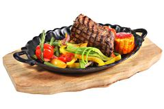 Mexican steak with vegetables in cast iron oval serving platter. - stock photo