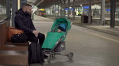 Parents sitting near the station and plays with baby  Stock Footage