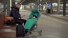 Upset Father with kid waiting on station , cellphone  Stock Footage