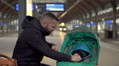 Father plaing with the baby on station, looks watch Stock Footage