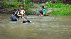 Family relaxing in the cool water of a river at Phnom Kulen National Park Stock Footage