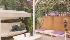 Beautiful girl reading a book on the swing in the garden. Large video. - stock footage