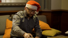 Man with santa cap sitting on the sofa and giving somethink  Stock Footage